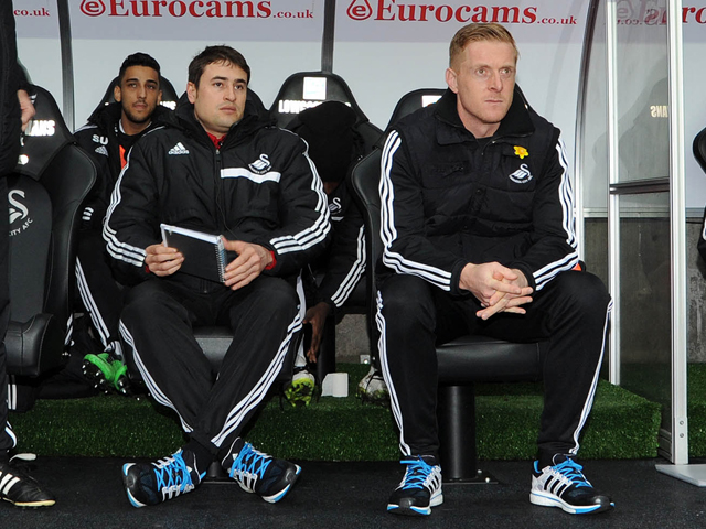 Swansea city's manager Garry Monk (c) with his coaching staff sits in dugout ahead of k/o. Barclays Premier league, Swansea city v Crystal Palace match at the Liberty Stadium in Swansea, South Wales on Sunday 2nd March 2014. pic by Andrew Orchard, Andrew Orchard sports photography. contact and payments to Andrew Orchard, 2 Old Vicarage close, Pengam, Blackwood, Gwent. NP12 3TU. Tel 07974 069129.  vat reg no 615 9784 04,   no unpaid use, All usage chargeable. if self billing, bacs to  20 10 26,  20034991,  Barclays