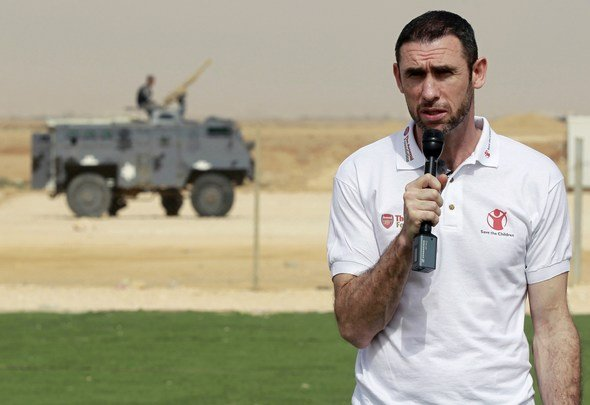 Martin Keown, a former British soccer player for Arsenal, speaks to Syrian refugee children during the official opening of Save the Children's new soccer field at the Al Zaatri refugee camp in the Jordanian city of Mafraq, near the border with Syria, May 2, 2013. Keown's visit is part of soccer club Arsenal's global partnership with humanitarian group Save the Children's education projects. REUTERS/Muhammad Hamed (JORDAN - Tags: SPORT SOCCER ENTERTAINMENT SOCIETY EDUCATION)  Picture Supplied by Action Images
