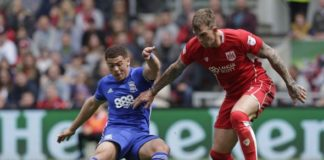 Aden Flint of Bristol City looks to avoid a sliding challenge