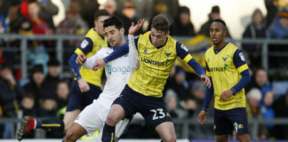 Ryan Ledson battles for the ball for his English club Oxford United